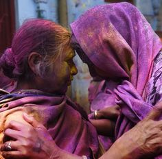 Two Indian widows touch their foreheads as they celebrate Holi, or 'festival of colors' in Vrindavan on 3 March 2015.