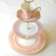 Pale candy pink is the sweetest shade for a tiered tea stand of vintage china! Waiting for cupcakes, this display is first in a series of 3