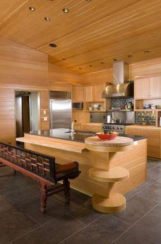 Modern kitchen. Bench seating, island, glass tile backsplash, island sink.