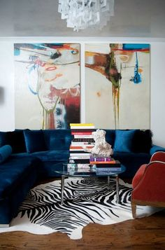 Room Decor Ideas: a young living room full of color. The white wall is hidding with two giant painting. The velvet dark blue sofa gives life to the room with the zebra print rug. The final touch is the round center table.