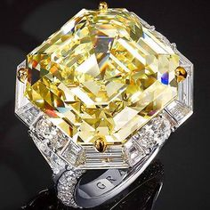 GRAFF High Jewelry ring with a 33.15 carat emerald cut yellow diamond stone, surrounded by oval, baguette and brilliant cut diamonds.
