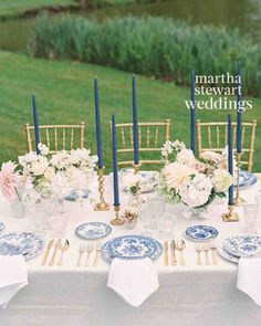 Centerpieces of dahlias, roses, scabiosa, sweet peas, and hydrangeas decorated tables along with blue taper candles in brass holders.