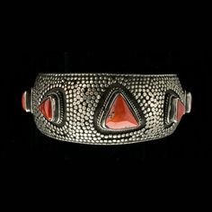 Vintage tribal cuff bracelet from India. Solid sterling silver with a granulated surface and 7 triangular bezel set red coral stones.The stone are graduated in size from 15mm to 8mm. This is an impressive bracelet, beautifully handcrafted and in pristine condition. We believe this is a Rajasthani piece because of the granulation style,   Inside Circumference: 5 1/2 Gap: 1-3/8 Total circumference: 7 Weight: 69.7 grams Band width at center: 1 3/16 Stones: Red coral metal: 900+ tested   SKU…
