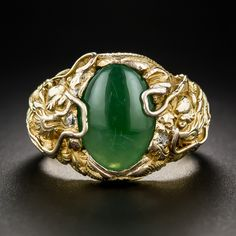 A shiny spinach green jadeite cabochon (for some reason not quite as nice as it looks in our photo with the directed lighting), is closely guarded left and right by a pair of fierce Chinese dragons, each bearing a tiny twinkling diamond in its jaws. The artful repousse style details continue all around the size 9 1/4 ring shank. Exotically handsome.