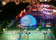 Rising Moon, un pabellón luminoso armado con 7 mil botellas plásticas que representa un hemisferio de la luna y que refleja la otra mitad en la laguna del parque.