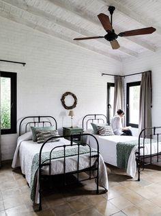 Dormitorio sobrio de una casa de campo con techo de madera pintado de blanco; camas individuales de hierro con almohadones aqua y tejidos, y mantas al tono, de Prágmata.