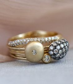 Loose, organic shapes of gold glitter with splashes of diamonds in the Glasgow Stack. The wavering bands and pebbles of encrusted gold create a perfectly imperfect artistic look for the everyday. Alternating widths and antique rhodium accents make these diamond stacking rings shine apart from the rest!