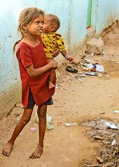 A little girl looks after her brother in the slums of Kochrab India,,,Save children in 2015!