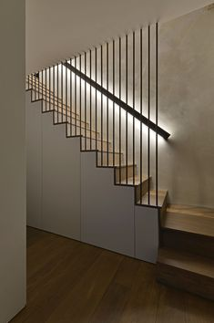 These modern wood stairs have a handrail with hidden lighting, and a floor-to-ceiling steel rod safety barrier. Square Feet Architects have designed modern stairs that have handrails with hidden lighting, and floor-to-ceiling steel rods safety barriers. Wood Stair Handrail, Stair Railing Design, Home Stairs Design, Staircase Railings, Stair Decor, Wood Stairs, Interior Stairs, House Stairs, Staircase Ideas