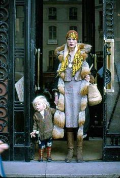 """Willy van Rooy and her son Alejandro in Paris, 1970/71: """"I never remember her following fashion or buying clothes off-the-rack... What I love about this picture is that it really shows her style, the mix of old-Hollywood glamour (the 30′s vintage coat, the red lips, the short snake-skin jacket), with absolute freedom (the embroidered dress, the hand-made spanish boots, the Ibiza basket, the scarf and the flowing hair)."""""""