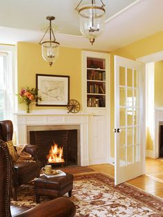 25 Cheery Ways to Use Yellow in Your Decor White millwork, soft yellow walls, honey wood floors, cognac leather wing chairs: this is my Dream Room! Room Paint Colors, Paint Colors For Living Room, Wall Colors, Yellow Paint Colors, Color Yellow, Home Living Room, Living Room Designs, Cozy Living Room Warm, Cozy Room