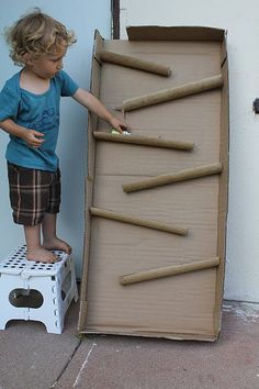 old cardboard box w/ paper towel rolls cut in half lengthwise, glued on. roll cars or balls down for lots of entertainment!