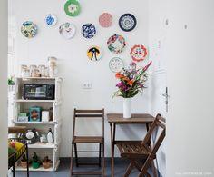 Cozinha tem azulejos brancos, mesa e cadeiras de madeira e composição de pratos na parede.