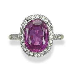 A FINE RUBY AND DIAMOND RING   Set with a modified octagonal-cut ruby, weighing approximately 5.43 carats, with circular-cut diamond surround and shoulders, mounted in platinum and gold