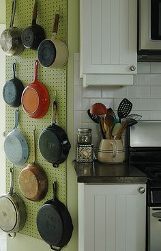pegboard pot rack.- The majority of my pots-and-pans no longer take up valuable drawer space   my cookware couldn't be closer to the stove — I just turn on the burner and grab what I need. The wall rack allows me to use pans as color in the kitchen — my favorite is the tomato-red vintage Dansk enameled cast iron that my friend Sarah found on a Goodwill run. The whole project cost about $20 .