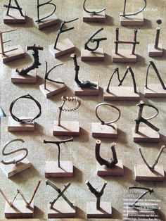 Alphabet made of twigs on wooden blocks. (just an image, no further info). Cute way to learn letters.
