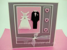 A lovely way to showcase premade bride and groom attire on colors that match the wedding theme.  Several layers of pink, grey and cream highlight the bride's dress and the groom's tux on this handmade wedding card. Pink pearl hearts and a sheer bow add the finishing touches.