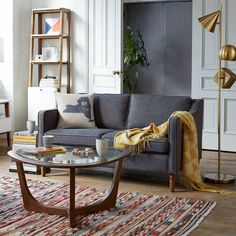 Mid-Century style meets globalist in this living room. Inspired by 1950s furniture silhouettes, our Hamilton Sofa is an instant classic. It's perched on solid poplar wood legs and covered in textured tweed, a durable fabric that ages well.