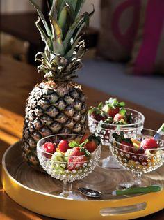 Detalle de la mesa del quincho de una casa. Bandeja de madera redonda con cuchara de mango verde y copas de cristal tallado. En ellas, ensalada de frutas con kiwi, frutilla y ananá.