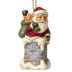 4053829 Santa In Chimney (Hanging ornament)- Perched on a chimney with his colourful bag full of toys; this festive Santa is on a mission to deliver in this magical ornament from the artistry of Jim Shore #Christmas #magical #festive