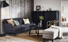 A living room with a grey STOCKSUND sofa, ARKELSTORP storage in black and a KRAGSTA black coffee table.