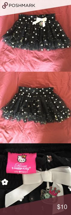 Princess Hello Kitty black sparkling tutu skirt This is an adorable black tutu skirt in all over metallic sparkling flowers and dots, with elastic smocked waistband and pretty light grey bow with hello kitty face trim on the bow. Cute to wear to any occasions! Never worn so looks like new! Hello Kitty Bottoms Skirts