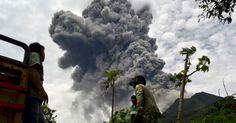 18.set.2013 - Fazendeiros se apressam para colher grãos no distrito de Karo, na Indonésia, enquanto o vulcão Sinabung expele cinzas. Milhares de moradores próximos do vulcão fugiram nesta terça e quarta-feira (18) depois que o Sinabung entrou em erupção, expelindo rochas e cinzas quentes Imagem: Sutanta Aditya/AFP