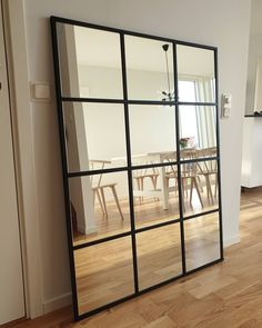 Image may contain: indoor Dining Room Mirror Wall, Window Mirror Decor, Mirror Wall Art, Diy Mirror, Ikea Mirror Hack, Industrial Mirrors, Small House Interior Design, Faux Window, First Apartment Decorating