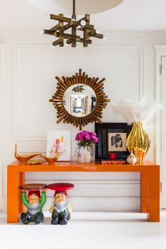 Simon Doonan - An whimsical entryway vignette of two gnomes beneath a lacquered orange table with assorted objets