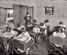 Vintage Photo of a School Room While the Children Are Looking At Their Books As the Teacher Watches Over Them, & a Young Girl With a Suspicious Grin on Her Face