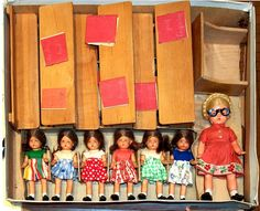 German school play set with girl doll students, teacher doll with pinned up blond braids and awesome glasses, double desks, books, and teacher's desk.  Date not noted.