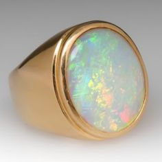 This incredible vintage mens ring features a massive and vibrant white opal cabochon bezel set in heavy 18k yellow gold. This is an awesome ring that would look great on a larger hand. We can re-size it to fit. I wouldn't recommend going much smaller than a size 10.