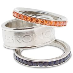 Enjoy this official NFL licensed Denver Broncos ring. A great gift for any Denver Broncos fan!Ladies' ringTeam color stacked rings - set of threeFeatures the team logo and team color crystals on a stainless steel bandAvailable in sizes Broncos Gear, Denver Broncos Football, Go Broncos, Broncos Fans, Football Baby, Cincinnati Bengals, Broncos Merchandise, Broncos Colors, Ring Set