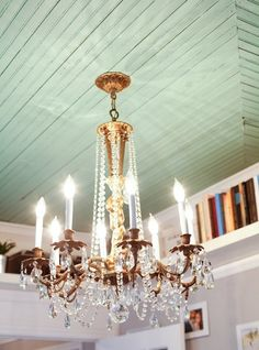 Turquoise beadboard ceiling and pretty crystal chandelier.