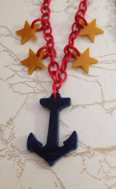 My patriotic bakelite blue moon swirled anchor and butterscotch star necklace has a bright red celluloid chain, I love it!