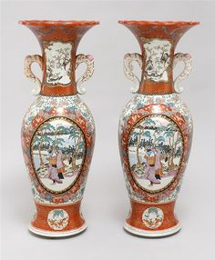 "PAIR OF IMARI PORCELAIN VASES Meiji Period In baluster form with elephant's-trunk handles and floriform trumpet mouths. Decoration of figural landscapes with Mt. Fuji on a floral ground. Heights 34.5"" (87.4 cm)."
