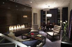 LOVE: exotic wood fireplace + muted palette + channel back chairs.  Presidential Suite at The Hazelton Hotel designed by Brian Gluckstein