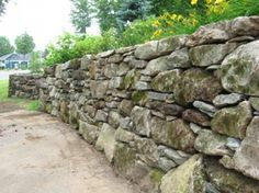 These mossy stones make a new wall in Bromont, QC look as though it has been around for a hundred years.  These stones replaced an earlier wall built with stones too small to hold back the bank.