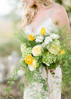 Add a touch of yellow to your bouquet full of greenery to complete your spring wedding.