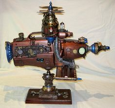 "Made of found objects. It's about 24"" long , with a unique stand. This would make a special addition to your Steampunk decor. This is the only air ship I've attempted. Hand painted using metallic finishes."