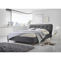 The Gennadios Mid-century Modern Grey Fabric Grid-tufting Platform Bed boasts a low contemporary design and features a chic curved headboard with beautiful grid-tufting detailing