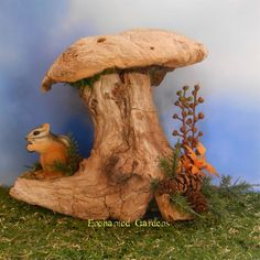 A mini woodland cottage with a tiny chipmunk in the fairy garden.