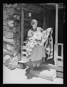 Mrs. Bill Stagg exhibiting a quilt made from tobacco sacks which she ripped up, dyed, and pierced. Nothing is wasted on these homesteading farms. Pie Town, New Mexico