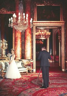 Cecile Beaton photographing Queen Elizabeth, wearing the order of the garter, at Buckingham Palace, 1953.