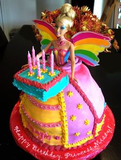a Barbie cake in which the Barbie is wearing a princess gown, has rainbow wings, and is holding out a birthday cake with candles, labeled 'Happy Birthday, Princess Misty!'