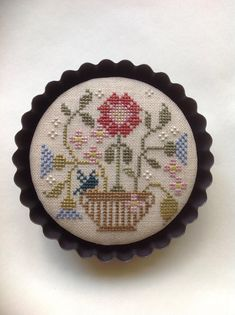 Cross stitched floral piece mounted in tart pan. Brenda