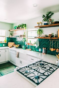 White cabinets, open wood shelves, lots of plants, deep green-blue backsplash: Moon to Moon