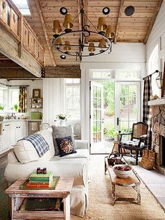 A combination of wood paneling and milk white tongue-and-groove paneling keeps this living space looking simply charming and sweetly rustic. A compass-style iron chandelier illuminates the sitting area while a stone fireplace