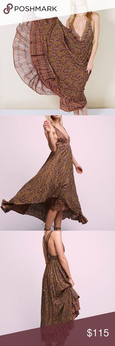 FREE PEOPLE RHYTHM OF LOVE DRESS Style: 39314877 Color Code: Printed flowy maxi dress featuring a plunging neckline with crisscross strap detailing with metal accents.  Elastic band at the waist for an easy fit with an adjustable belt.  Lined.  100% Rayon.  Hand Wash Cold.  Color: metallic Free People Dresses Maxi