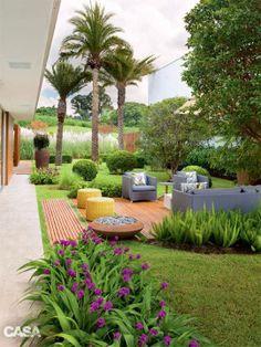 Jardim gramado com deck de madeira na área dos móveis